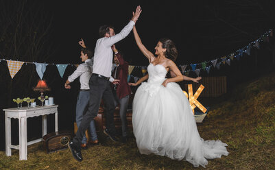 Happy bride jumping and giving high five with young man on a night field party with friends - DAPF00943
