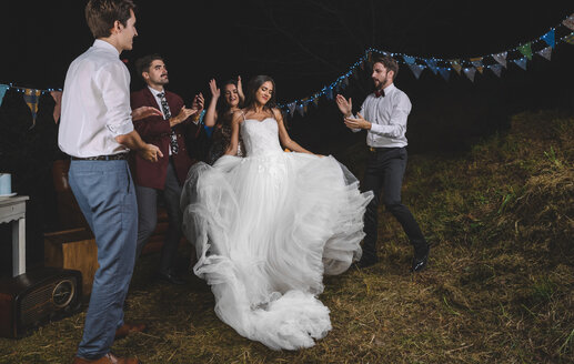 Happy bride dancing and having fun while her friends clapping on a night field party - DAPF00946