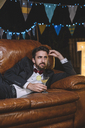 Pensive man in suit lying on sofa on a night party oitdoors - DAPF00952