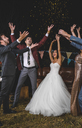Cheerful wedding couple and friends raising their arms while confetti falling over their heads on a night party outdoors - DAPF00955