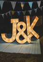 Handmade wooden letters illuminated with light bulbs on a night field party - DAPF00958