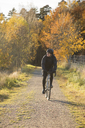 Mature man riding bicycle on dirt road through autumn forest - FOLF05546