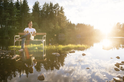 Man sitting on bench in middle of lake - FOLF05588