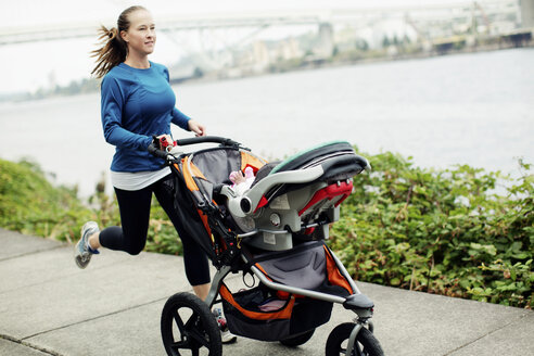 Woman running with baby stroller on footpath by river in city - CAVF31166