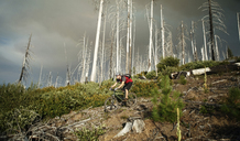 Low angle view of man cycling on field against bare trees - CAVF31238