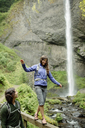 Man looking at girlfriend walking on railing by waterfall - CAVF31256