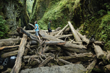 Couple walking on logs amidst rock formations in forest - CAVF31259