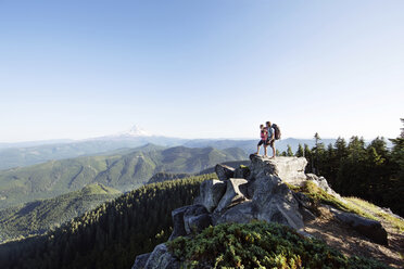 Couple standing on mountain against clear sky - CAVF31265