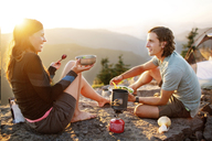 Happy couple having food while sitting on mountain against clear sky - CAVF31268