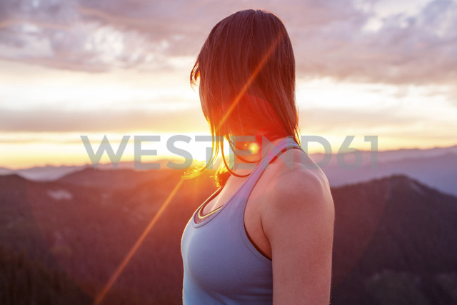 Side view of woman looking through shoulder while standing on mountain against cloudy sky during sunset - CAVF31292