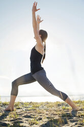 Woman practicing warrior pose at beach against clear sky - CAVF31298