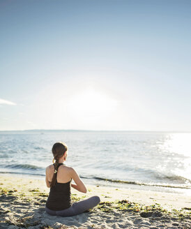 Rear view of woman meditating at beach against sky during sunny day - CAVF31301