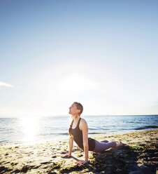 Woman practicing cobra pose at beach against sky during sunny day - CAVF31304