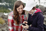 Happy female friends using mobile phone while standing on mountain - CAVF31319