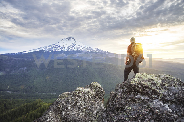 Rear view of hiker looking at view while standing on mountain against cloudy sky - CAVF31331