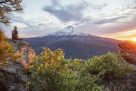 Hiker looking at view while sitting on mountain during sunset - CAVF31334