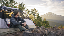 Male hiker looking away while sitting in tent against sky - CAVF31340