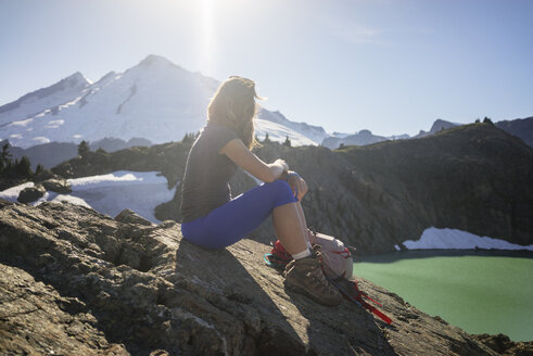 Female hiker sitting on mountain against sky during sunny day - CAVF31343