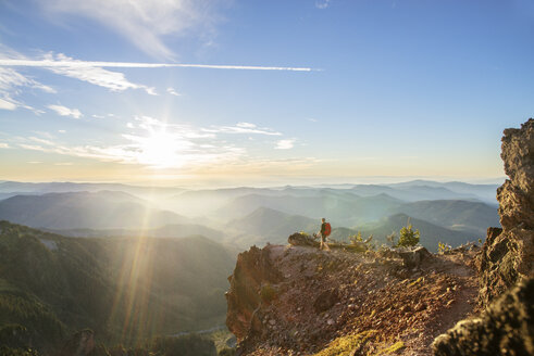 Male hiker standing on mountain against sky during sunny day - CAVF31355