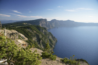 Scenic view of Crater Lake by mountains against sky during sunny day - CAVF31361