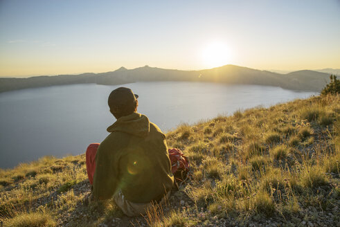 Rear view of hiker looking at view while sitting on mountain during sunset - CAVF31364