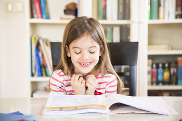 Portrait of happy little girl doing homework - LVF06841
