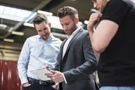 Three men sharing tablet on factory shop floor - DIGF03546