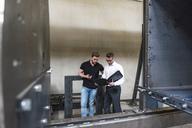 Two men with folder talking on factory shop floor - DIGF03573