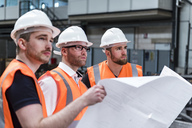 Three men wearing hard hats and safety vests holding plan in factory - DIGF03579