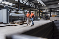 Two men wearing hard hats and safety vests walking on factory shop floor - DIGF03582