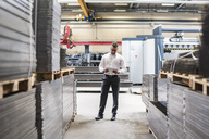 Businessman with tablet standing on factory shop floor - DIGF03585
