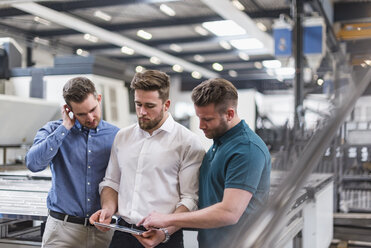 Three men sharing tablet on factory shop floor - DIGF03615