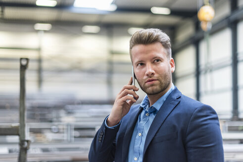 Portrait of confident businessman on cell phone in factory - DIGF03633