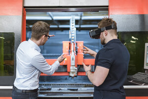 Man explaining machine to colleague wearing VR glasses in factory - DIGF03642