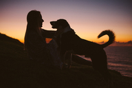 Side view of woman sitting with dog on hill against sky during sunset - CAVF31384