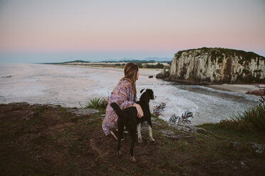 Side view of woman crouching by dog on hill at beach during sunset - CAVF31387