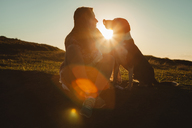 Woman and dog looking at each other while sitting on hill during sunset - CAVF31390