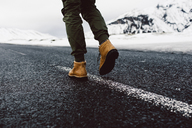 Low section of man walking on road during winter - CAVF31402