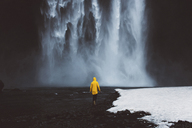 Rear view of man walking towards waterfall during winter - CAVF31405