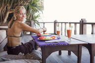 Rear view portrait of woman having fruits on balcony at tourist resort - CAVF31477