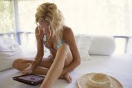 Sensuous woman using tablet computer in gazebo - CAVF31483