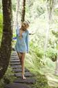 Sensuous woman walking on boardwalk in forest - CAVF31489