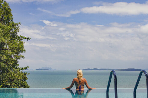 Woman enjoying sea view while relaxing in infinity pool - CAVF31495