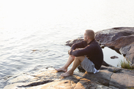 Mature man sitting on rocky lakeshore in the Stockholm archipelago - FOLF05740