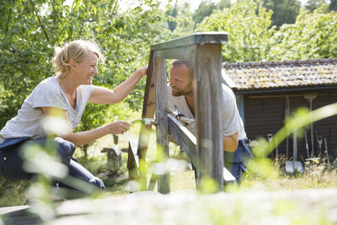Mature man and mature woman painting wooden railing - FOLF05743