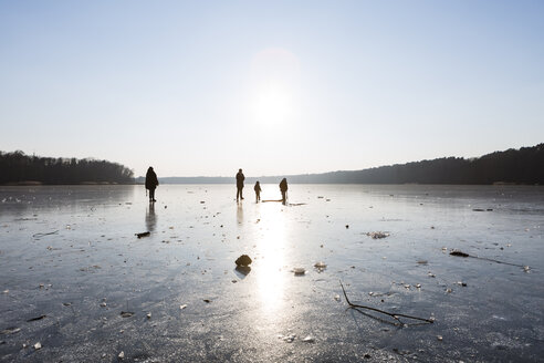 Germany, Brandenburg, Lake Straussee, frozen lake and silhouettes of people walking on ice - OJF00248