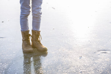 Germany, Brandenburg, Lake Straussee, feet with boots on frozen lake - OJF00251