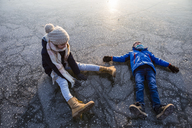 Germany, Brandenburg, Lake Straussee, two kids sitting and lying down on frozen lake - OJF00254
