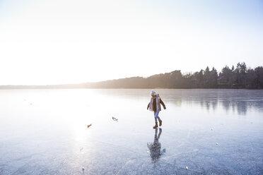 Germany, Brandenburg, Lake Straussee, girl walking on frozen lake - OJF00257