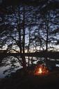 Mid adult men sitting around campfire at dusk - FOLF05851